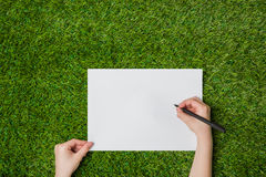 Writing on blank sheet of paper over green grass Royalty Free Stock Images