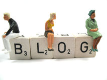 Writing a blog. Several figurines sitting on the word blog royalty free stock images