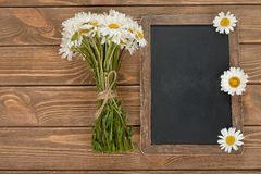 Writing board and daisies Stock Photos