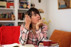Writing a book. Young female book author sitting on her desk.  thinking and looking at distance Royalty Free Stock Photo
