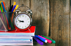 Writing-books, an alarm clock and school tools. Royalty Free Stock Photos