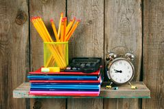Writing-books, an alarm clock and school tools . Royalty Free Stock Image