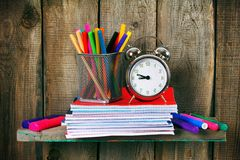 Writing-books, an alarm clock and school tools. Stock Photography