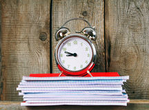 Writing-books and an alarm clock . Stock Images