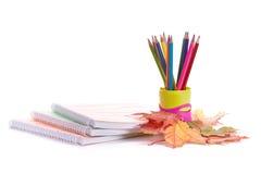 Writing-books, multi-coloured pencils and autumn leaves. Stock Photos