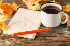 Writing-books, multi-coloured pencils in a cup and autumn leaves Royalty Free Stock Photos