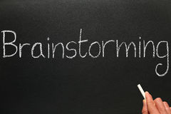 Writing brainstorming on a blackboard. Writing brainstorming with chalk on a blackboard Stock Photography