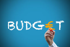 Writing budget. Hand with orange pen writing word budget with euro symbol over blue background Stock Images