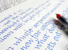 Writing calligraphy on paper with blue ink Royalty Free Stock Image
