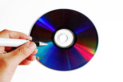 Writing on a cd. A man is writing something on a colorful cd Stock Photo