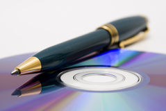 Writing a CD. A pen and a CDROM stock photo