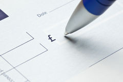 Writing a check. Writing a UK Sterling blank check with a blue pen, focus is on the pen point Royalty Free Stock Image