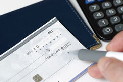 Writing check. Closeup on man`s hands writing a check Royalty Free Stock Photos