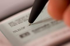 Writing a Check. Hand and pen make out a check stock photos