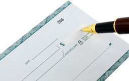 Writing a check with ballpoint pen. Writing a check in US Dollars with a ballpoint pen, white background Royalty Free Stock Photos