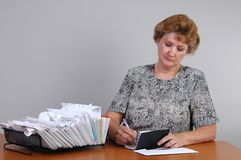 Writing a Check. A woman writes a check to pay bills Royalty Free Stock Photography