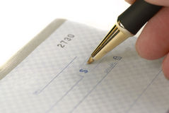 Writing Check in Checkbook. Person writing check with pen and checkbook royalty free stock images