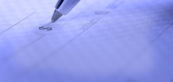 Writing Check in Checkbook. Person writing check with pen and checkbook royalty free stock image