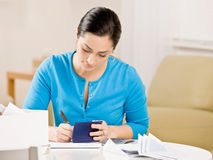 Writing check from checkbook to pay monthly bills. Woman writing check from checkbook to pay monthly bills