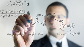 Writing chemical formula. Man with glasses writing chemistry formulas over a virtual transparent screen Stock Photography