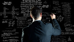 Writing chemical and physical formulas. Man writing chemistry and physics formulas over a blackboard Stock Image