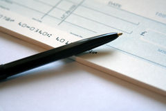 Writing a Cheque. Cheque and Pen royalty free stock photo