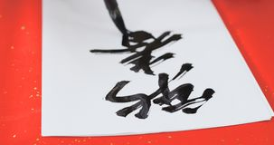 Writing Chinese calligraphy for lunar new year, phrase meaning f stock photos
