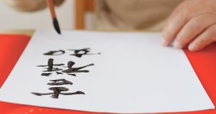 Writing Chinese calligraphy with phrase meaning wish you good fo Stock Images