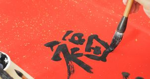 Writing chinese calligraphy with word meaning luck for lunar new. Year Royalty Free Stock Photo