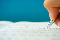 Writing Chinese characters on paper with a fountain pen Royalty Free Stock Image