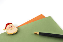 Writing christmas cards. Two envelops with santa claus and a pen Stock Photo