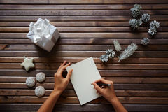 Writing Christmas regards. Female hands with pen over piece of paper with spice-cakes, decorative silver cones, giftbox and white toy star near by Stock Image