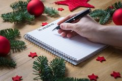 Writing Christmas wish list with title I would like in German on. A notepad with Christmas decorations and fir branches on a wooden table seen from the side Royalty Free Stock Photos