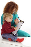Writing on clipboard young woman and little girl Stock Images