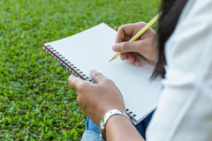Writing. Closeup woman sitting on the grass and going to write something on notebook Stock Images