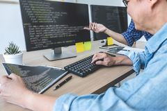 Writing codes and typing data code technology, Two professional programmer cooperating working on web site project in a software royalty free stock image