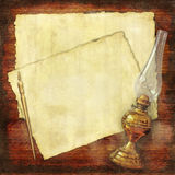 Writing collage with vintage oil lamp. Two paper sheets with scalloped edges, a pen and an old oil lamp on a wood grunge bench royalty free stock images