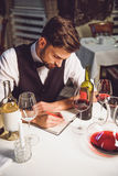 Writing comment about wine collection. Sommelier is sitting neat table, hardly composing recall in notebook among variety of white and crimson nectar Royalty Free Stock Photography