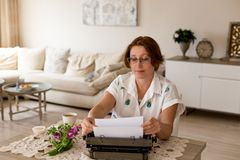 Writing concept. Female author working using her retro typewrite stock image