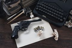 Writing a crime fiction story - old retro vintage typewriter and revolver gun with ammunitions, books, blank paper, old ink pen. On wooden table royalty free stock photo