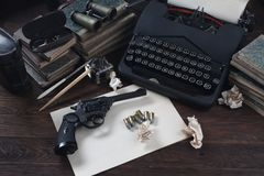 Writing a crime fiction story - old retro vintage typewriter and revolver gun with ammunitions, books, blank paper, old ink pen. On wooden table stock images