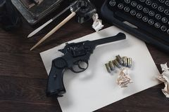 Writing a crime fiction story - old retro vintage typewriter and revolver gun with ammunitions, books, blank paper, old ink pen. On wooden table stock photos