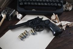 Writing a crime fiction story - old retro vintage typewriter and revolver gun with ammunitions, books, blank paper, old ink pen. On wooden table stock photography