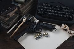 Writing a crime fiction story - old retro vintage typewriter and revolver gun with ammunitions, books, blank paper, old ink pen. On wooden table royalty free stock images