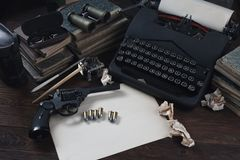 Writing a crime fiction story - old retro vintage typewriter and revolver gun with ammunitions, books, blank paper, old ink pen. On wooden table stock photo