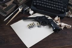 Writing a crime fiction story - old retro vintage typewriter and revolver gun with ammunitions, books, blank paper, old ink pen. On wooden table royalty free stock photography
