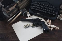 Writing a crime fiction story - old retro vintage typewriter and revolver gun with ammunitions, books, blank paper, old ink pen. On wooden table royalty free stock photos