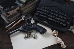 Writing a crime fiction story - old retro vintage typewriter and revolver gun with ammunitions, books, blank paper, old ink pen. On wooden table royalty free stock image