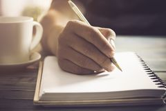 Hand of people, student writing and note on notebook on wood table with copy space, in library, concept as education attempt and m. Writing dairy on notebook in stock image