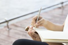 Writing dairy on notebook in park, concept as memory of life. And education royalty free stock photo